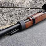 Mauser K98 PCP Ansicht links vorne mit Hawke Airmax 6-24x50 Compact Zielfernrohr vor Mauer liegend