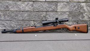 Mauser K98 PCP linke Seite Komplettansicht mit Hawke Airmax 6-24x50 Compact Zielfernrohr vor einer Mauer